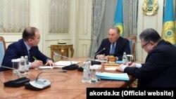 Президент Казахстана Нурсултан Назарбаев (в центре) во время встречи с министром информации и коммуникаций Дауреном Абаевым (слева). Астана, 26 февраля 2018 года.