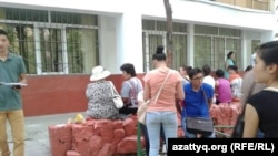 Ожидающие заселения студенты перед зданием общежития.