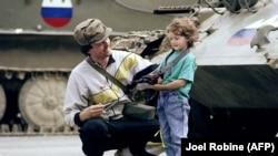 'Mi smo bili spremni. Mi smo mislili da ćemo ići izaći iz Jugoslavije ranije, ali smo čekali oružje, koliko ja znam.' (Slovenački vojnik i djevojčica pored tekova uzetih od JNA, 1991.)