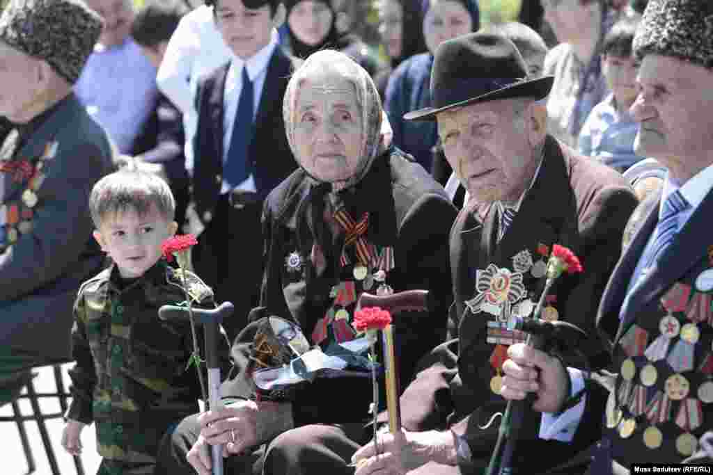 WW II veterans and a young boy watch the celebrations in Grozny.