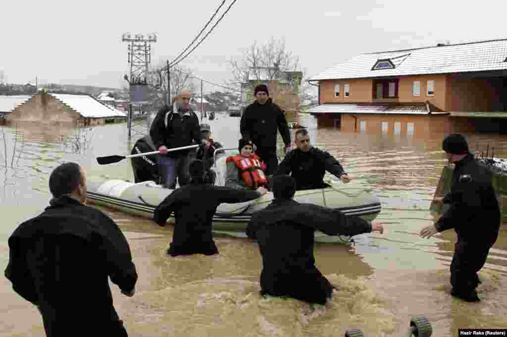 Members of the Kosovo Security Force rescue a woman whose house has been flooded since the night before, in the village of Zajm. (Reuters/Hazir Reka)