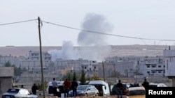 Smoke rises after a mortar lands in the Syrian town of Kobani, near the Turkish border, which has been besieged by Islamic State insurgents in recent days.