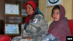 Справа - девочка, предположительно готовившаяся совершить атаку смертника. Слева - сотрудница афганской полиции. Гельменд, 6 января 2014 года.