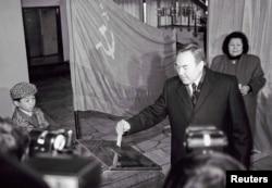 Кандидат в президенты Казахстана голосует на выборах 1 декабря 1991 года. Справа — его супруга Сара Назарбаева, слева — его внук Нурали.