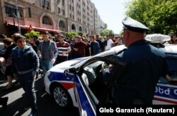 A policeman stands guard as supporters of Armenian opposition leader Nikol Pashinian stage a rally in Yerevan on April 25.