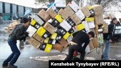 Алматы базарында жүк тасып жүрген адамдар. Көрнекі сурет.