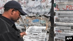 A Pakistani reads an Urdu-language newspaper in Karachi.