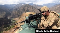 FILE: A U.S. soldier looks through his sniper scope in the province of Kunar in eastern Afghanistan.