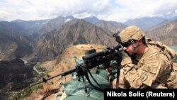 FILE: A U.S. soldier looks trough his sniper scope at a observation post in the eastern Afghan province of Kunar near the border with Pakistan.