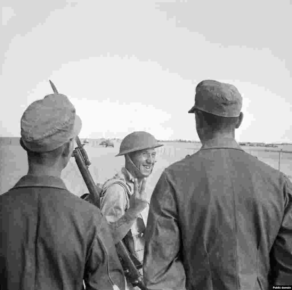 """A British soldier gives a two-fingered salute to captured German soldiers. Winston Churchill celebrated the victory in parliament, declaring, """"By a marvelous system of camouflage, complete tactical surprise was achieved in the desert."""""""