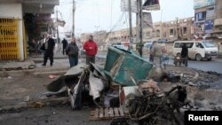 Iraqis inspect the site of a bomb attack in Baghdad, on January 14.