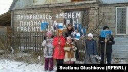 Дети и родственница Сандугаш Серикбаевой и Уюм Жолдасбаевой у своего дома, идущего под снос, держат портреты президента Казахстана. Астана, 11 ноября 2013 года.