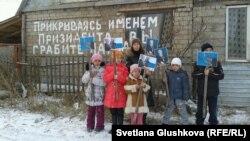Дети, живущие в доме на окраине Астаны, стоят с фотографиями президента Казахстана Нурсултана Назарбаева, они просят власти не сносить их дом. 11 ноября 2013 года.