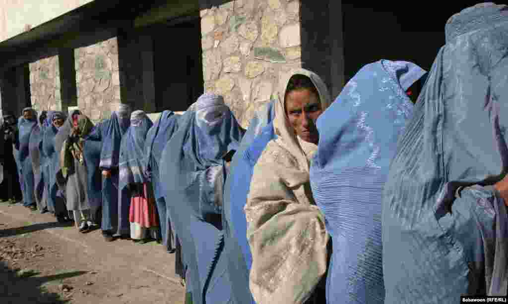Women wait in line to receive monthly food rations.