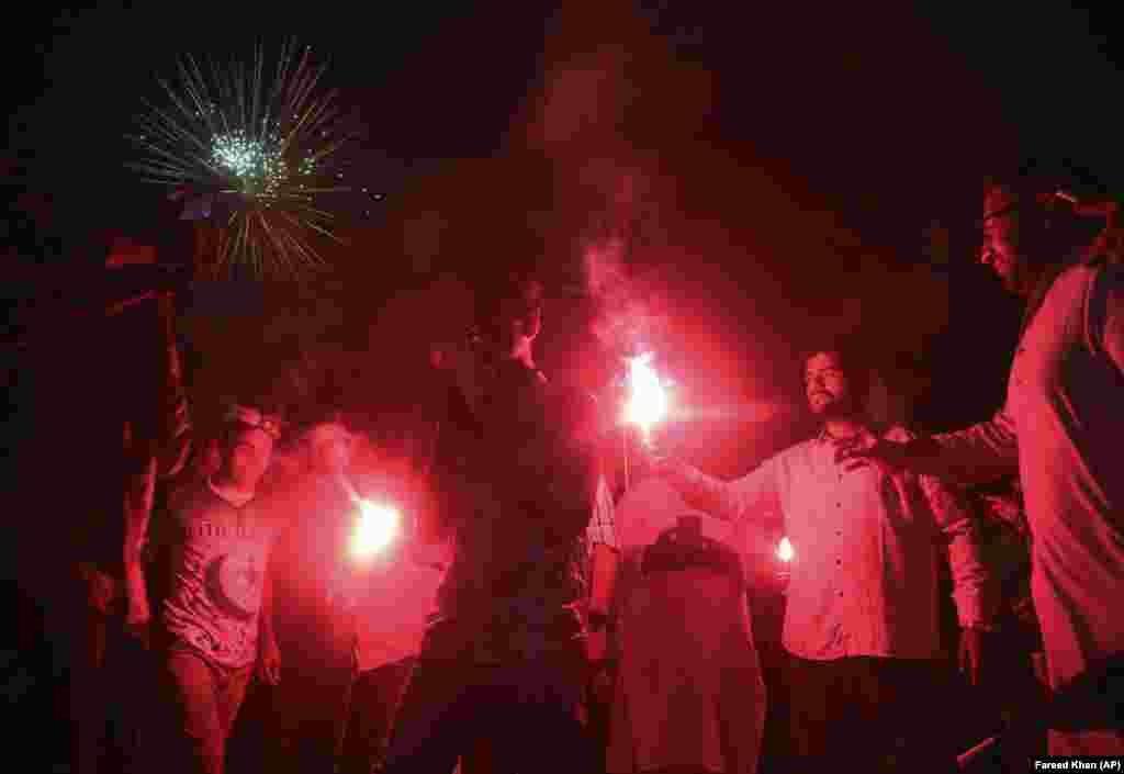 People light flares in Karachi.