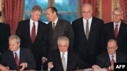 (Left to right:) Serbian President Slobodan Milosevic, Croatian President Franjo Tudjman and Bosnian President Alija Izetbegovic the sign Dayton peace accords in 1995 while U.S. President Bill Clinton, French President Jacques Chirac, German Chancellor Helmut Kohl, and U.K. Prime Minister John Major look on.