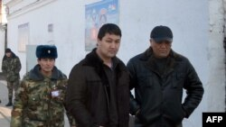 Кадыра Досонова (в центре) ведут для переговоров с начальством СИЗО во время тюремного бунта, Ош, 20 января 2012 года.