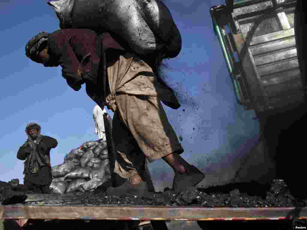 A laborer carries a sack of coal at a coal dumpsite outside Kabul. (Ahmad Masood for Reuters)