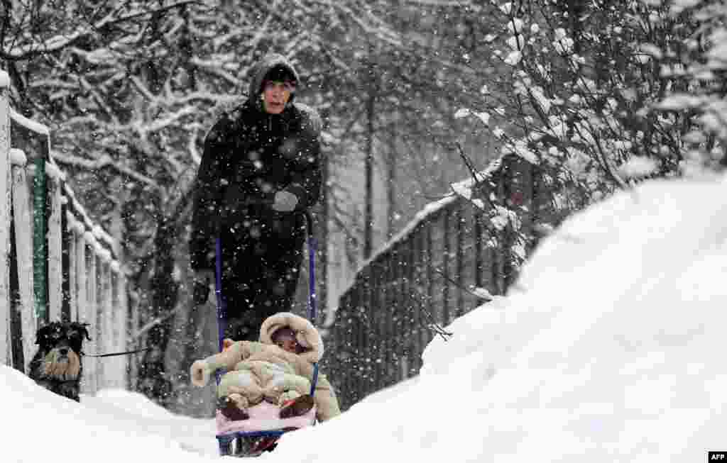 A woman walks with a child and dog in a snow-covered park in the Belarusian capital, Minsk. (AFP/Viktor Drachev)