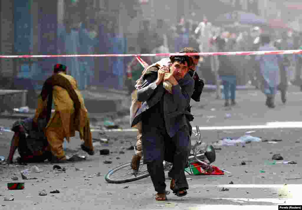 A man caries a wounded person to the hospital after a blast in Jalalabad, Afghanistan, on August 19. (Reuters/Parwiz)