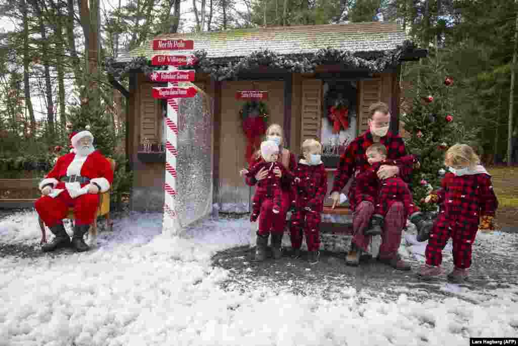Семья в рождественских костюмах позирует для фотографии с Санта-Клаусом, который находится за оргстеклом, чтобы уберечься от возможной опасности заразиться коронавирусом. Кингстон, Онтарио, Канада, 28 ноября 2020 года