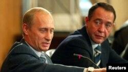 Михаил Лесин в бытность министром информации России слушает президента России Владимира Путина (слева). Владивосток, 24 августа 2002 года.