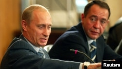 Russian President Vladimir Putin (left) gestures as Media Minister Mikhail Lesin listens to him during a meeting with local press in the far eastern city of Vladivostok in August 2002.