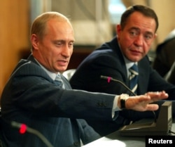 Russian President Vladimir Putin (left) with his Mass Media Minister Mikhail Lesin in Vladivostok in August 2002