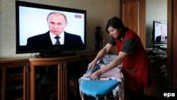 O femeie din Moscova calcă rufe în timp ce Vladimir Putin vorbește despre starea națiunii la televizor, 4 decembrie 2014