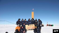 Russian researchers pose for a picture after reaching the subglacial Lake Vostok in February 2012 (file photo)