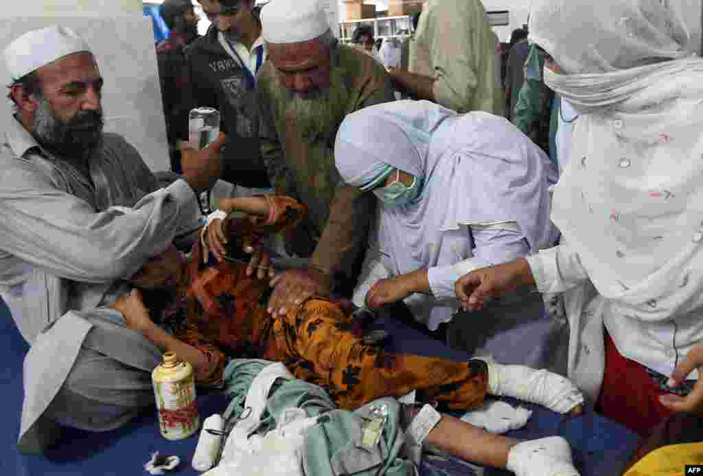 Pakistani paramedics treat an injured girl at a hospital in Peshawar.