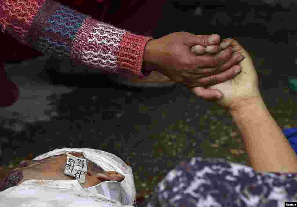 A woman holds the hand of a deceased relative who died during an earthquake outside a hospital in Kathmandu, Nepal. (Reuters/Adnan Abidi)