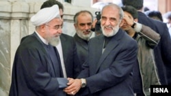 President Hassan Rouhani and conservative figure Hossein Shariatmadari greet each other. undated.