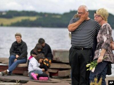 Ljudi i rođaci žrtava okupljeni tokom minute ćutanja u kampu Utoya, Norveška, 25. jul 2011.