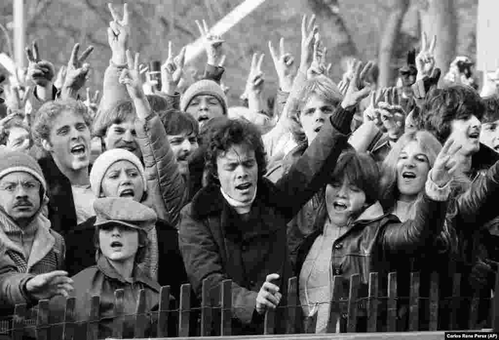 На цій фотографії з архіву від 14 грудня 1980 року люди, які беруть участь в данині пам'яті убитого музиканта Джона Леннона, підняли руки зі знаком миру і співають «Give Peace A Chance» («Дайте миру шанс») в Центральному парку Нью-Йорку, США