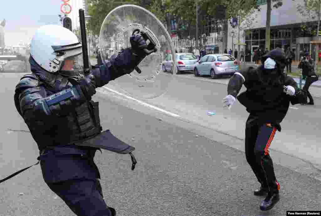 A demonstrator throws an object towards a police officer during a protest, organised by Black Lives Matter Belgium, against racial inequality in the aftermath of the death in Minneapolis police custody of George Floyd, in central Brussels, Belgium June 7, 2020.