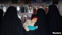 Женщина держит ребенка в магазине лагеря Аль-Хол, Сирия. 8 января 2020 года