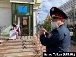 Баласын ертіп, пикет өткізіп тұрған Бақытгүл Мәсілбаеваны видеоға түсіріп тұрған полиция қызметкері. Нұр-Сұлтан, 16 қыркүйек 2020 жыл.