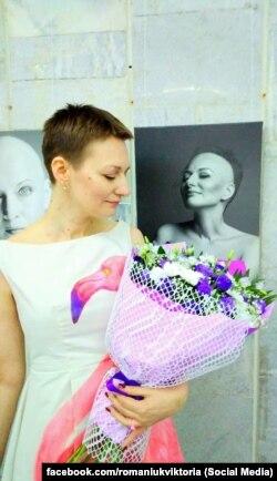 Вікторія Романюк на виставці «Без рожевих окулярів» поруч зі своїм чорно-білим фотопортретом