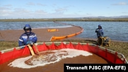 Workers fill a tank for collecting oil-water mixture from the water surface at the site of the spill into the Ambarnaya River outside Norilsk on June 7.