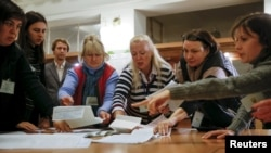 Election commission members count ballots after local elections at a polling station in Kyiv on October 25