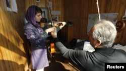 A teacher adjusts a student's violin work at the Kabul Music Academy.