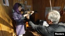 A teacher adjusts a student's violin work at the Kabul Music Academy.