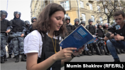 An activist reads the Russian Constitution out loud while surrounded by Russian riot police in Moscow on July 27.