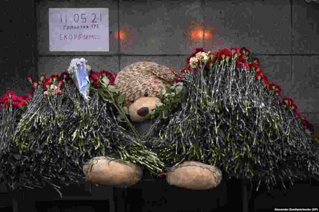 """A teddy bear and flowers with the poster reading """"11.05.21, School # 175, Mourn"""" in memory of the slain students in Kazan at the Tatarstan region's office in Moscow."""