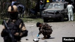 Security forces inspect the site of the explosion in Kabul on June 18 that was thought to have targeted ethnic Hazara lawmaker Mohammad Mohaqiq, Afghanistan's senior Shi'ite Muslim cleric.