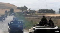 A convoy of armored personnel carriers and other military vehicles on a road leading out of the Georgian town of Gori in the direction of Tbilisi during the August 2008 fighting between Georgian and Russian forces
