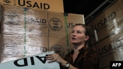 A USAID information officer shows American aid for Pakistani flood victims in 2010.