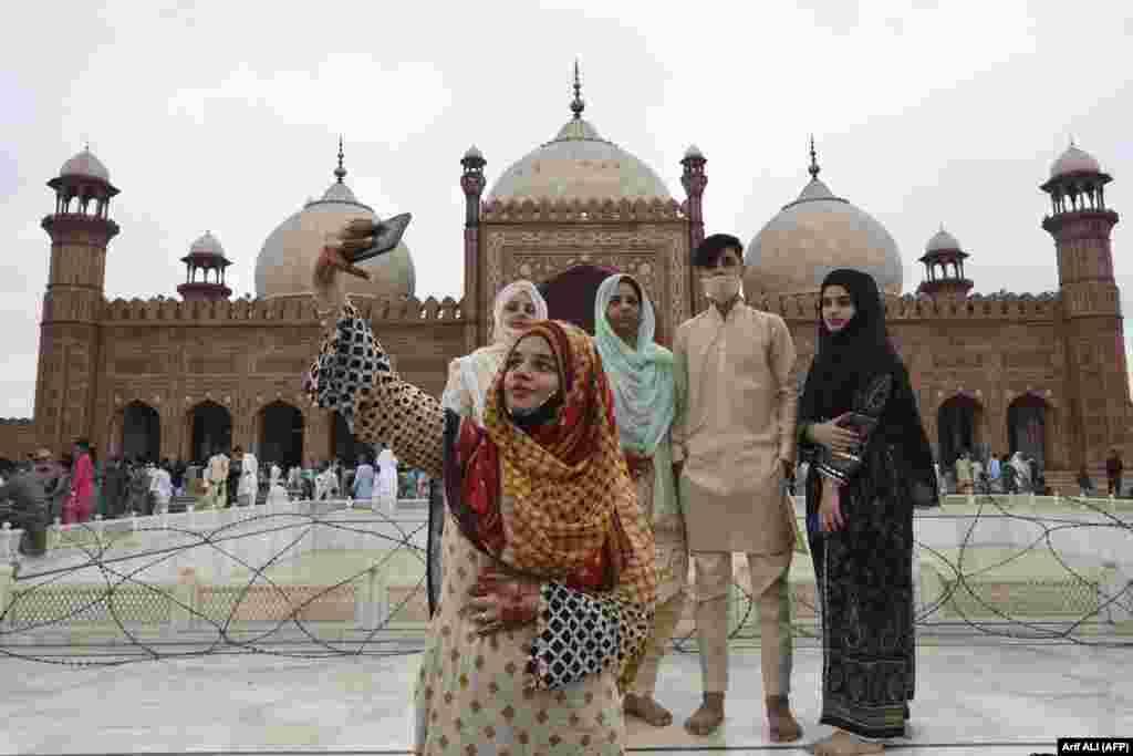 Женщина делает со своими друзьями селфи после молитвы в мечети в Лахоре, Пакистан