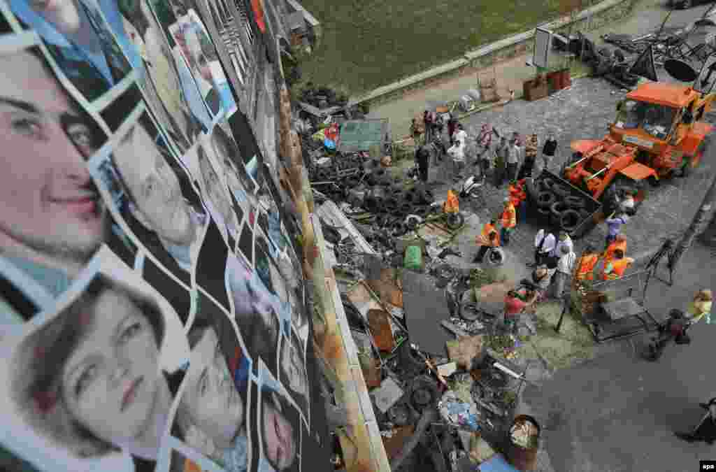 Pictures of people who were killed during the winter protests are attached to a bridge as municipal workers clean up a barricade on Independence Square in Kyiv on August 11, 2014. The downtown area of the Ukrainian capital was reopened after citizens had cleaned up the central streets two days previously.